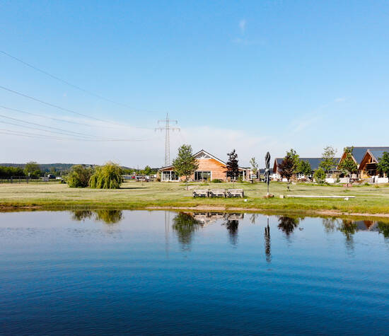 Blick vom See auf unser Hofcafé und das Bootshaus (Krewelshof Eifel)